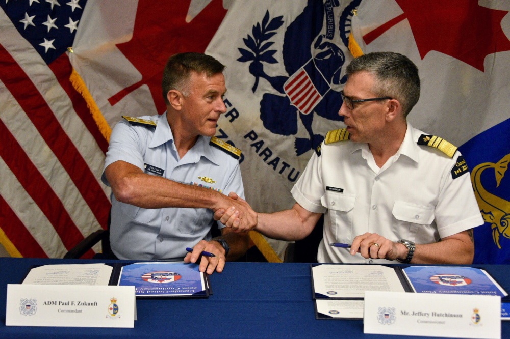 Adm. Paul Zukunft, U.S. Coast Guard commandant, and Mr. Jeffery Hutchinson, Canadian Coast Guard commissioner, shake hands after signing the Canada United States Joint Contingency Plan in Grand Haven, Michigan, Aug. 3, 2017. The joint contingency plan serves as a coordinated system for the two organizations to respond to incidents in shared waters along the boarder. U.S. Coast Guard photo by Petty Officer 1st Class Patrick Kelley.