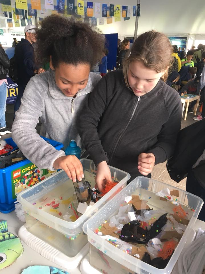 Students on a field trip use different strategies to remove litter from a miniature